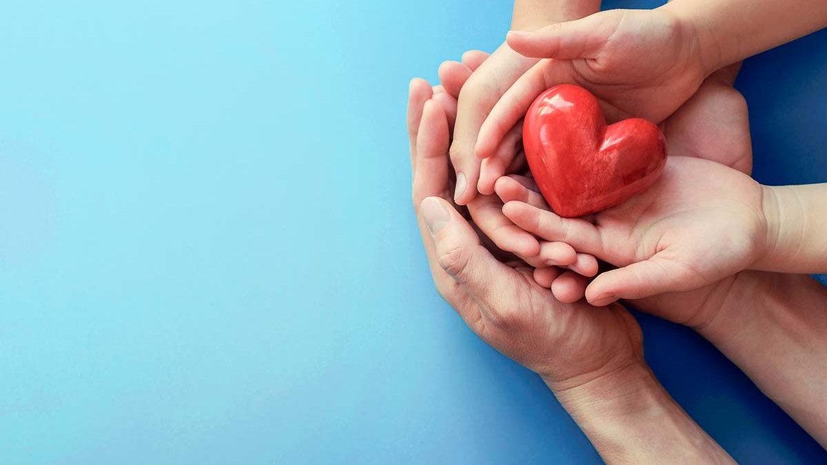 Sechs Hände, die vor blauem Hintergrund zusammen ein rotes Herz halten.