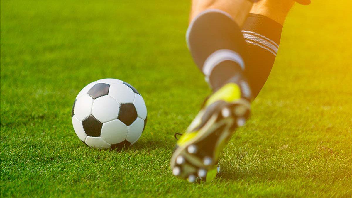 Fußballer mit schwarz-weißen Stutzen holt auf grünem Rasen mit dem linken Bein zu einem Schuss auf den vor ihm liegenden Ball aus.