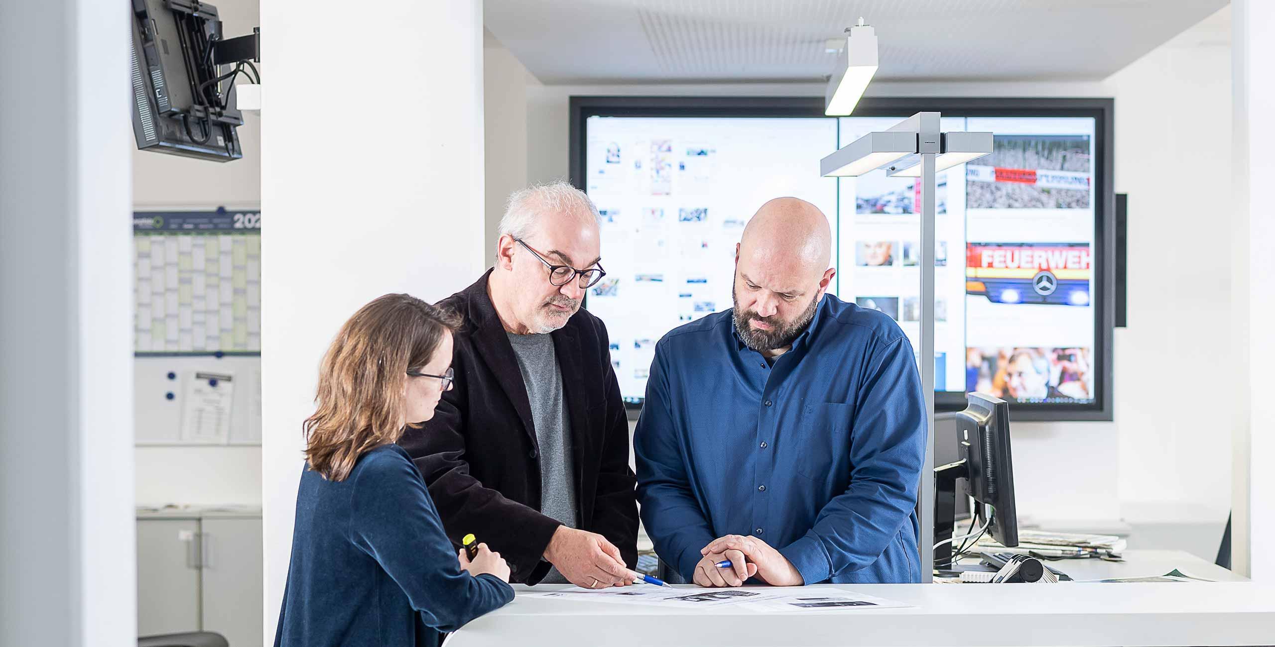 Drei Redakteure beraten sich an Schreibtisch über Magazine.
