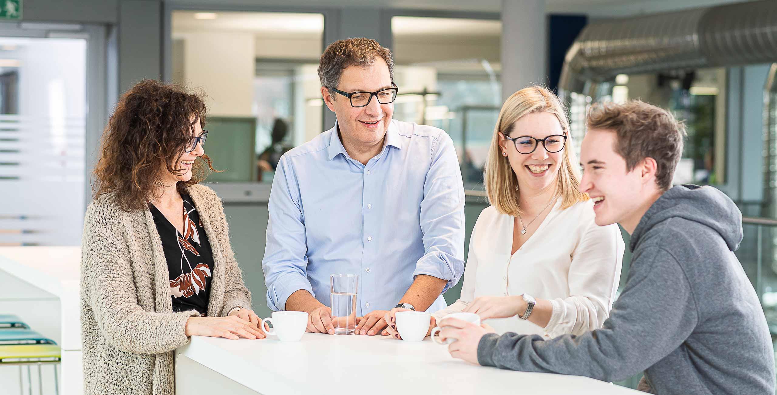 Vier Mitarbeiter von Oberpfalz Medien bei einem lockeren Gespräch über Karriere am Stehtisch mit Kaffee und Wasser.