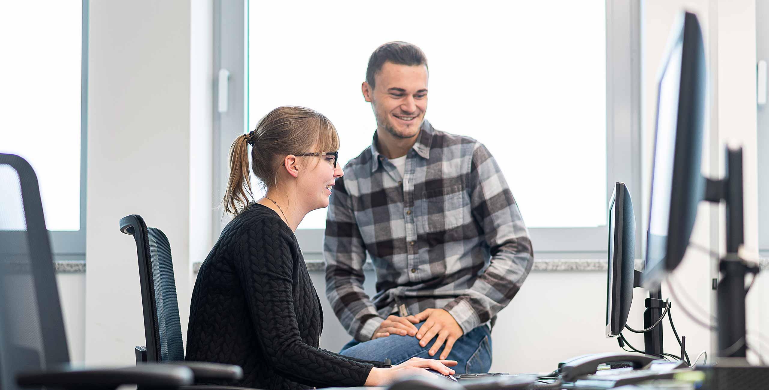 Zwei Mitarbeiter aus der Personalabteilung von Oberpfalz Medien beraten sich vor Computer über Dinge, die die Karriere betreffen.