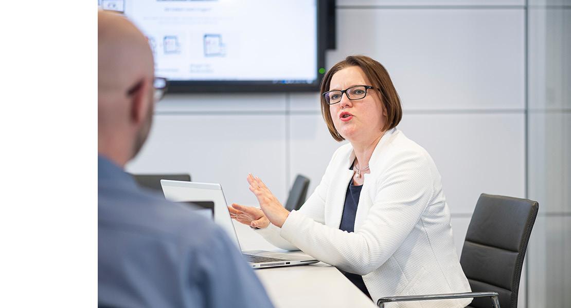 Gestikulierende Frau mit Brille und weißem Blazer vor Laptop am Schreibtisch bei der Beratung und Analyse.