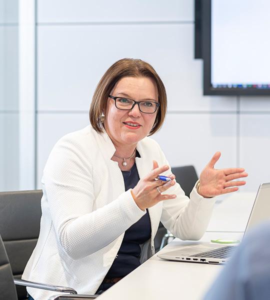 Gestikulierende Frau mit Brille und weißem Blazer vor Laptop am Schreibtisch bei der Beratung.