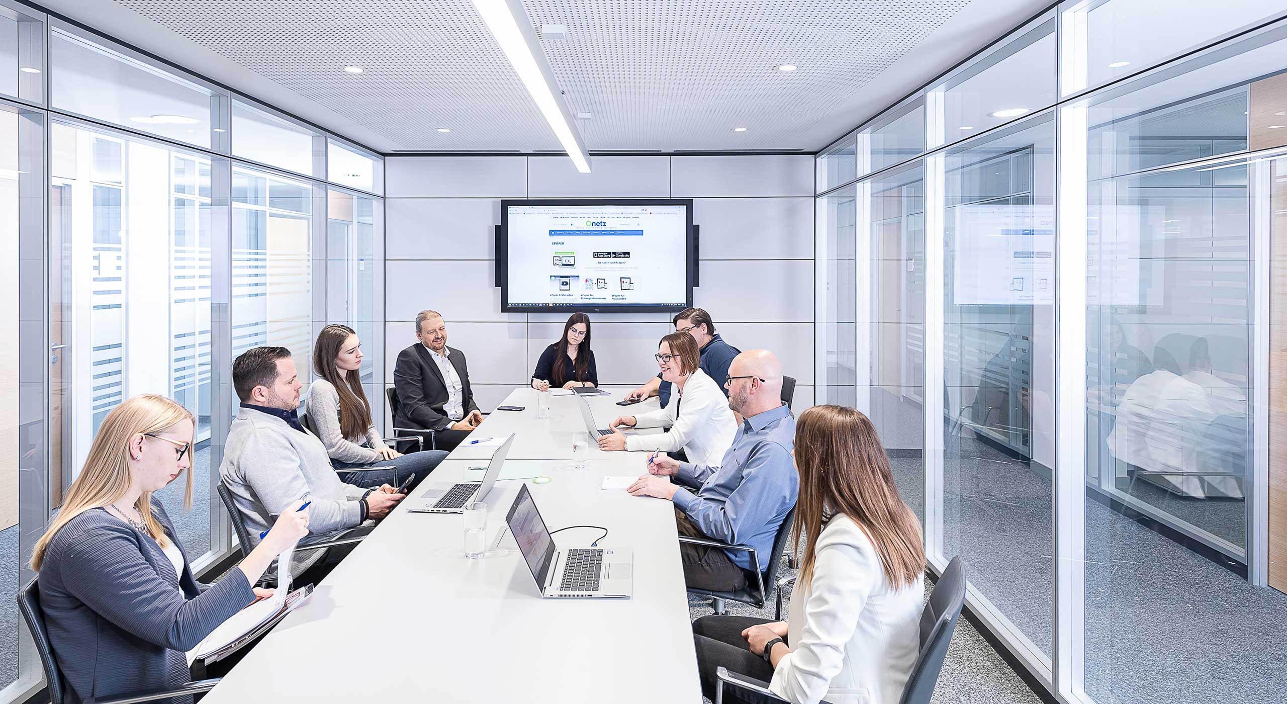 Neun Mitarbeiter von Oberpfalz Medien in einem Konferenzraum diskutieren an großem Tisch Leistungen, Beratung und Zielgruppen.