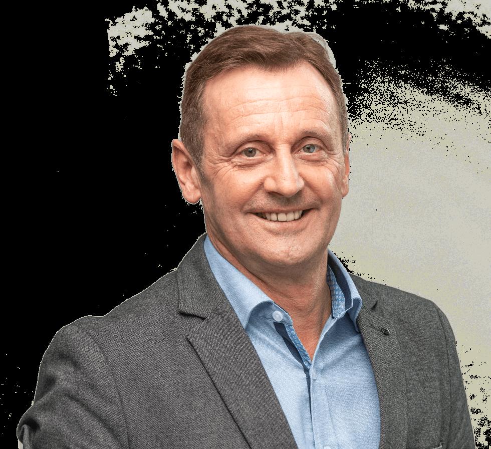 """Freigestellter älterer Mann, lachend, mit dunkelgrauem Jackett und kurzen hellbraunen Haaren, Person für den Markenwert """"Verbundenheit"""" von Oberpfalz Medien."""