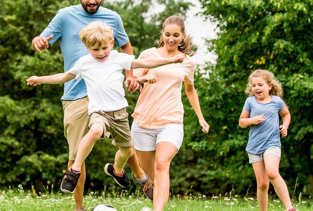 """Auf einer Wiese Fußball spielende Familie für die Beilage """"Ferien in der Region"""" von Oberpfalz Medien."""