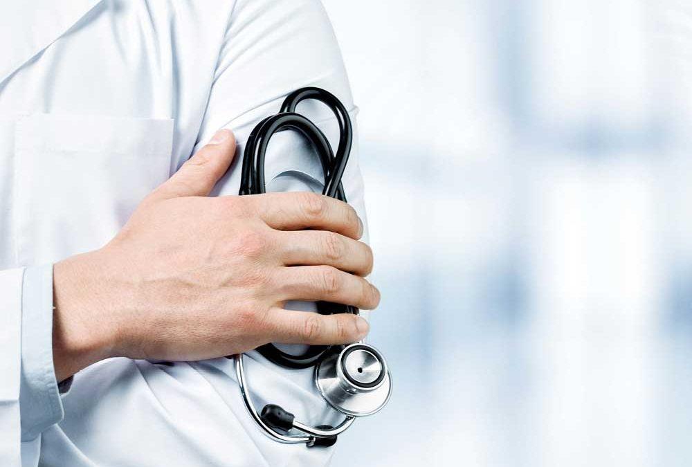 """Linke Oberkörperhälfte eines Arztes, der Stethoskop zwischen rechter Hand und linkem Oberarm hält, für das Magazin """"Expertenratgeber Gesundheit""""von Oberpfalz Medien."""