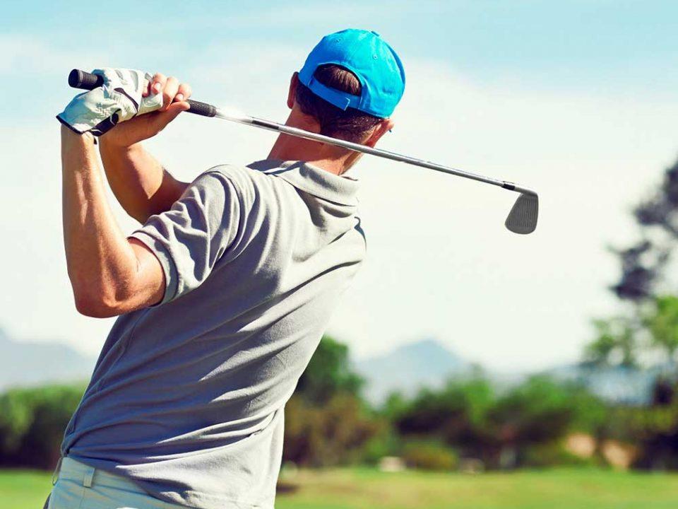 Ein Golfer von hinten, der seinen Golfschläger schwingt.