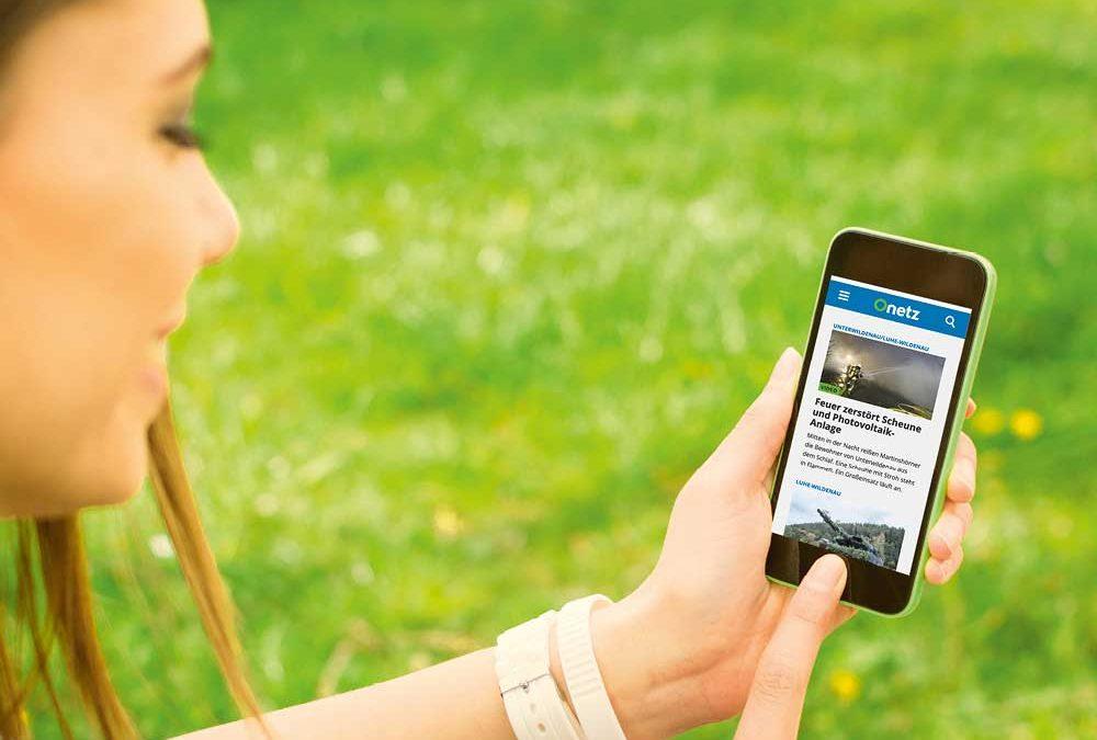 """Frau auf Wiese mit Smartphone in der Hand, auf dem das Onlineportal """"Onetz"""" von Oberpfalz Medien zu sehen ist."""