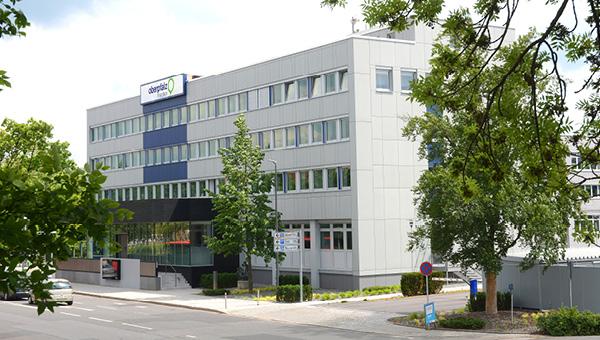 Verlagsgebäude von Oberpfalz Medien in Weiden von außen, grüne Bäume, Straße.