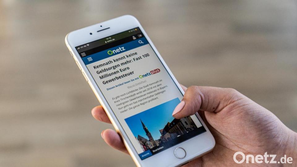 Mensch hält Smartphone mit dem Onetz in der Hand