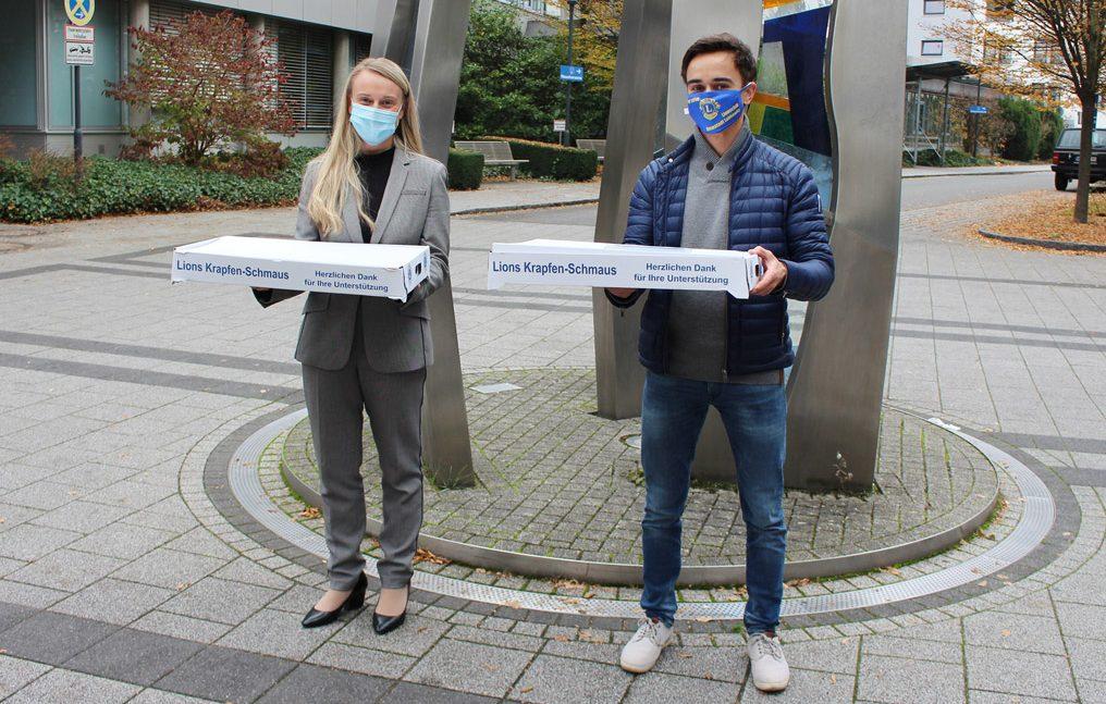 Zwei Menschen mit Boxen in der Hand vor dem Krankenhaus