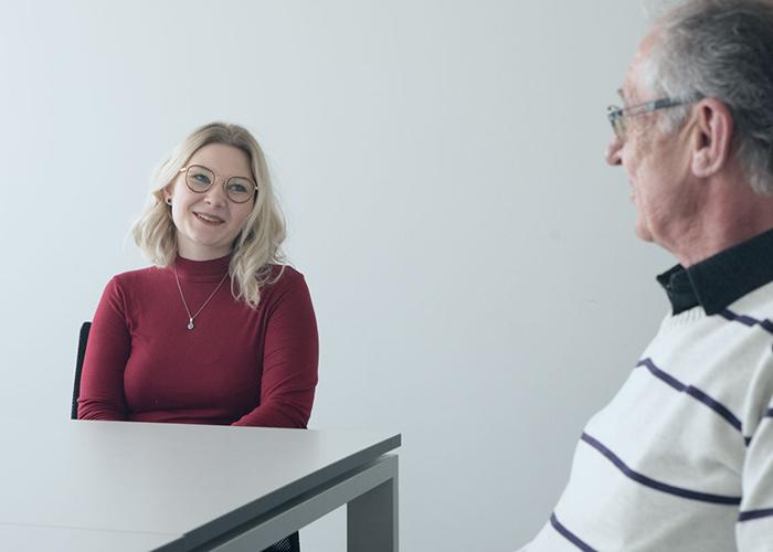Junge Mediaberaterin lacht im Gespräch mit Kollegen