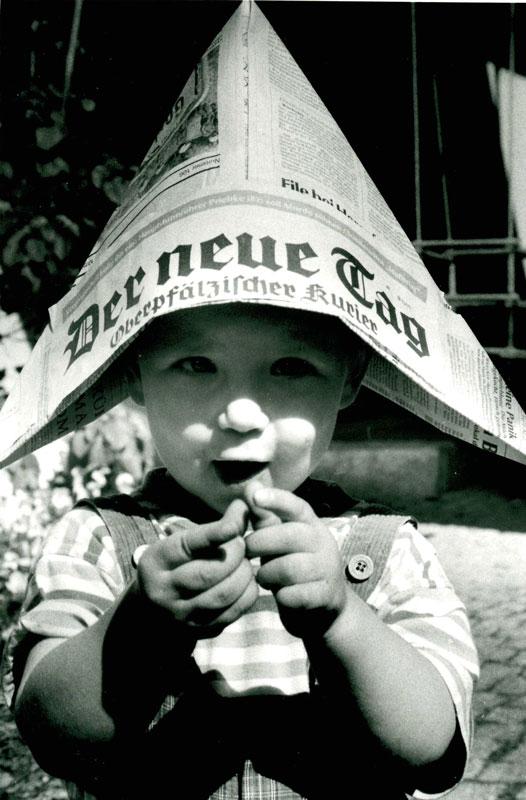 Kind mit Hut aus Zeitung der neue Tag