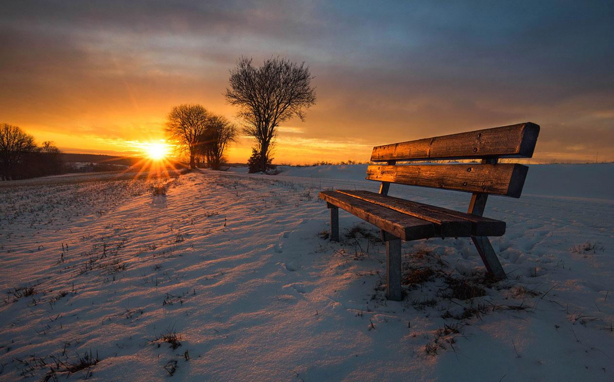 Fotografie von Bank im Schnee bei Sonnenuntergang