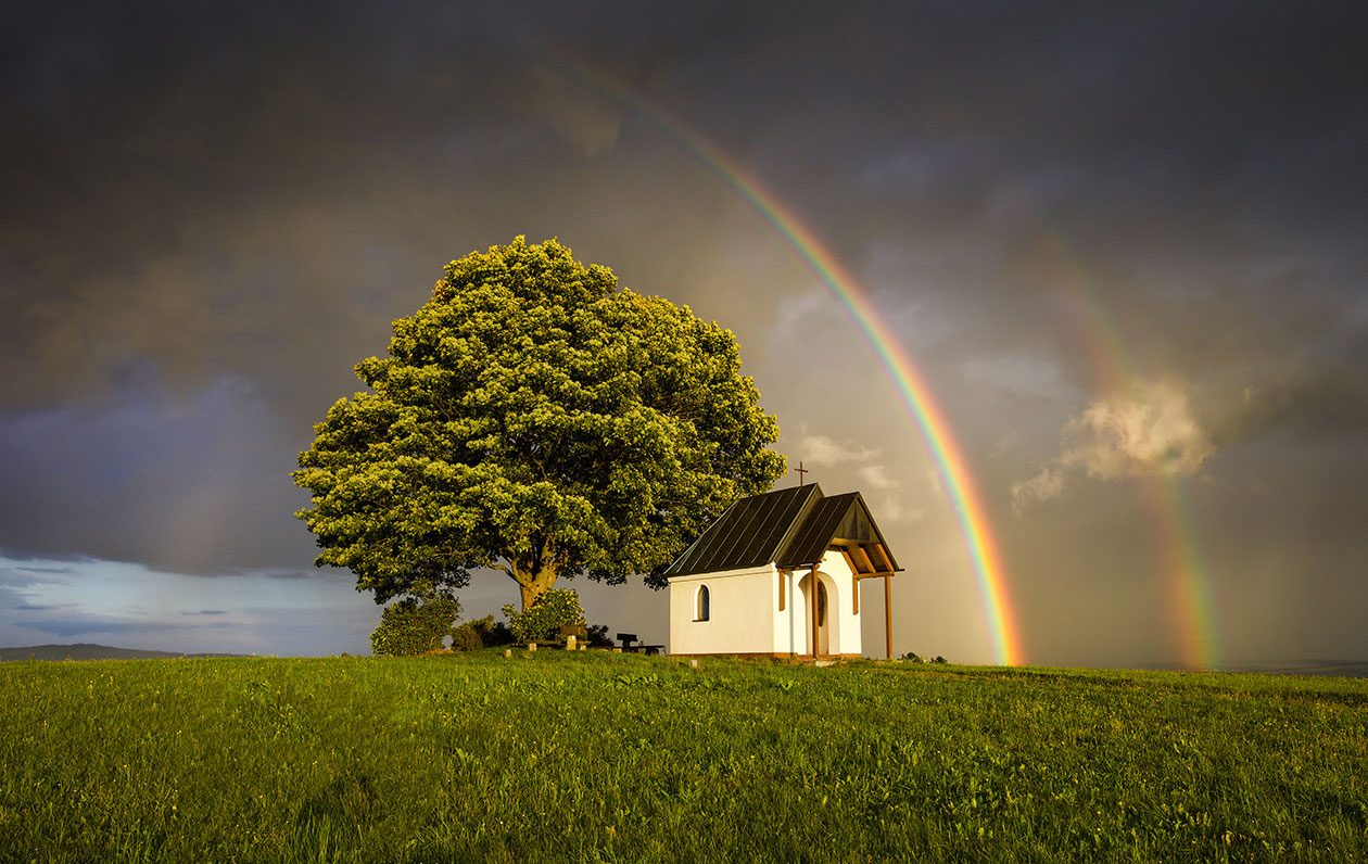 Landschafts-Fotografie einer Kapelle mit Baum vor Regenbogen