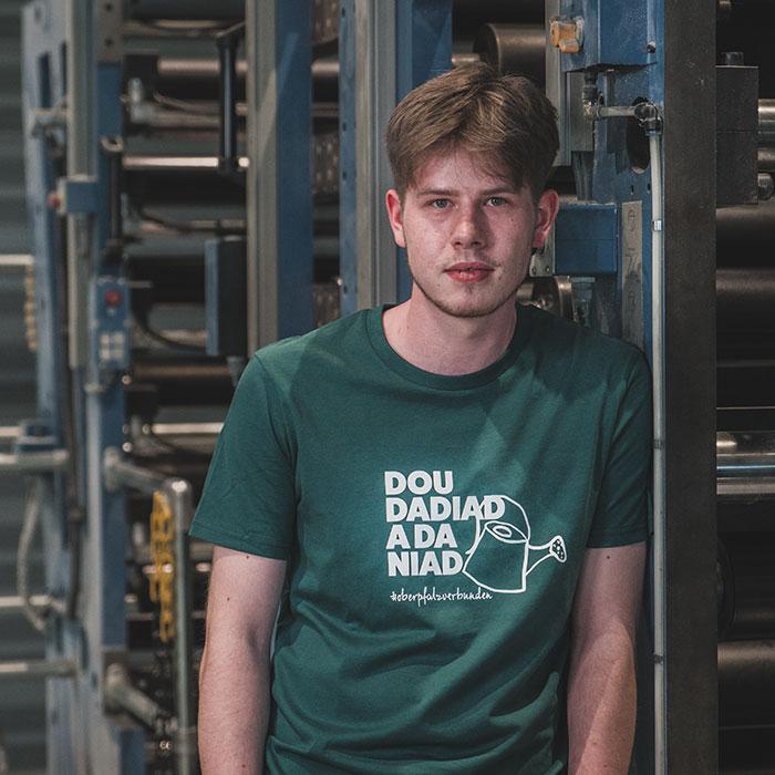 Junger Mann vor Druckmaschine trägt grünes T-Shirt