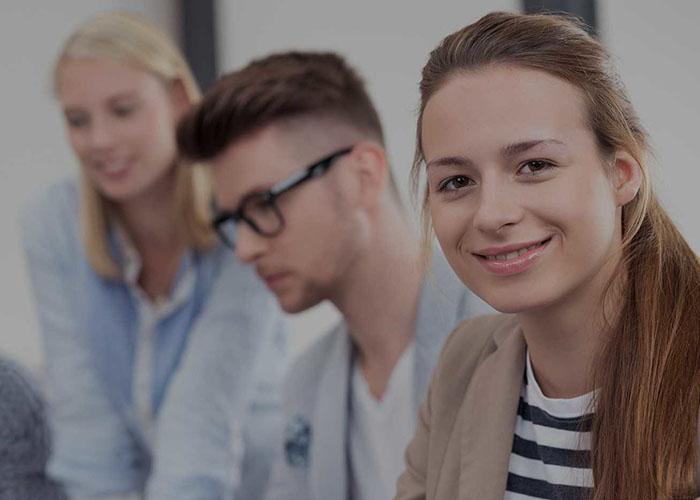Junge Frau sitzt mit anderen jungen Menschen am Tisch und lächelt in Kamera
