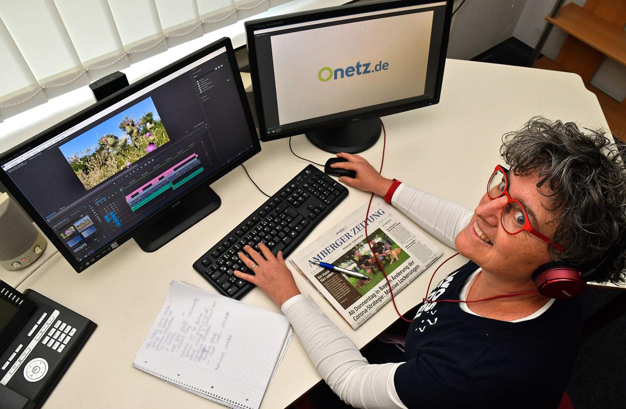 Reporterin sitzt in Multimedia-Büro mit zwei Bildschirmen